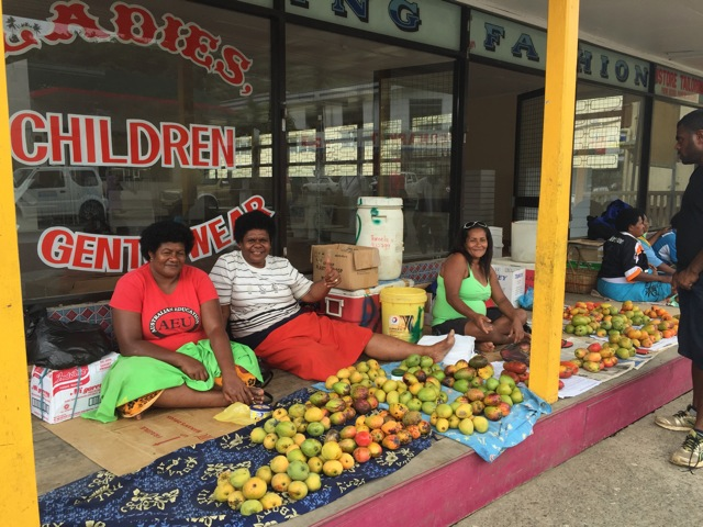 Women selling fruit outside of a shopfront